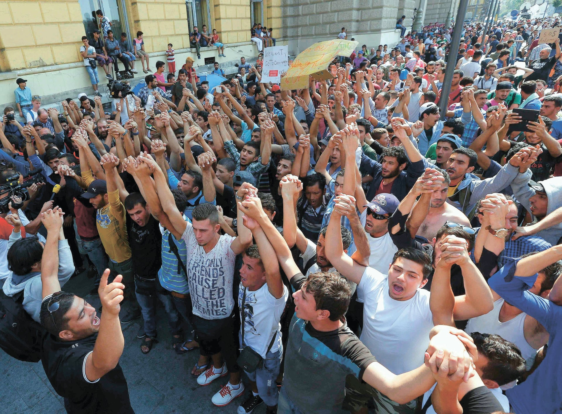 """Migrants protest outside the Eastern railway station in Budapest, Hungary, September 2, 2015. Hundreds of migrants protested in front of Budapest's Eastern railway station on Wednesday, shouting """"Freedom, freedom"""" and demanding to be let onto trains bound for Germany but the station remained closed to them. More than 2,000 migrants, including families with children."""