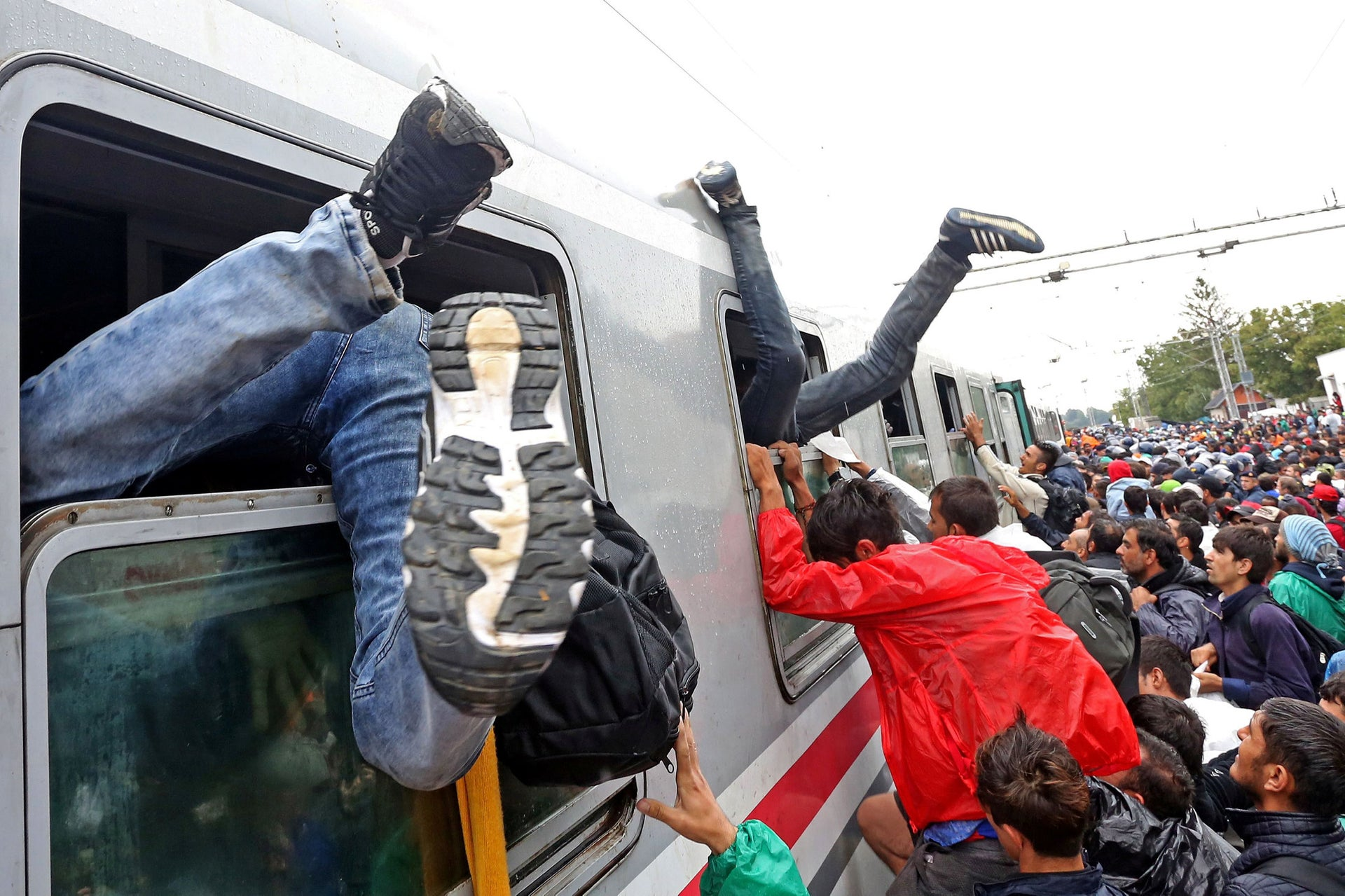 Migrants rush to board a train heading to the Hungarian border near the town of Botovo, at the train station in the eastern Croatia town of Tovarnik, on September 20, 2015.
