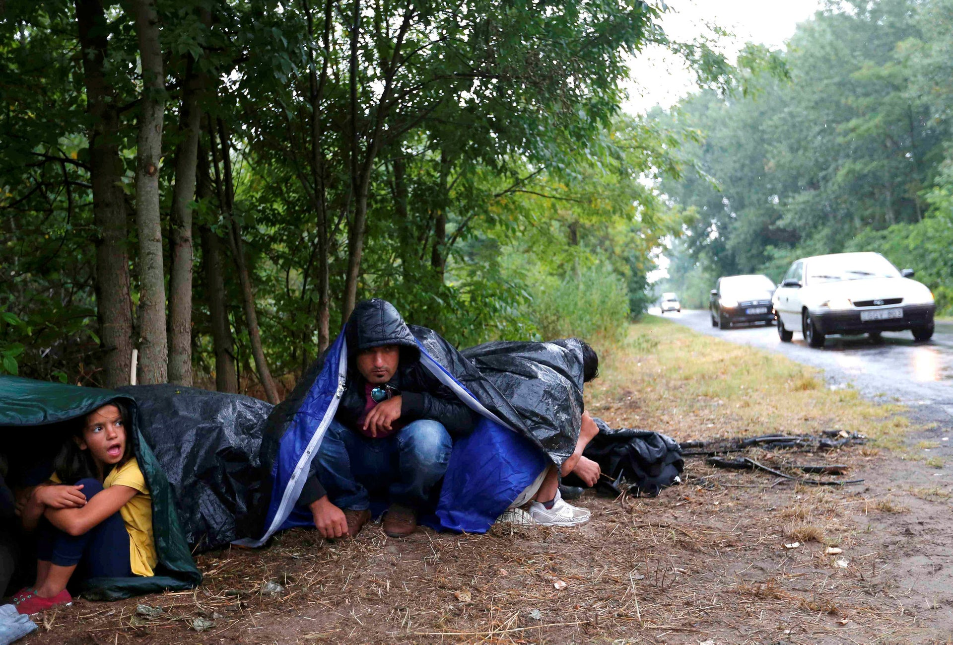 Migrants from Syria use sleeping bags to protect themselves from the rain as they rest on the side of a road after crossing the border illegally from Serbia, near Asotthalom, Hungary July 27, 2015.