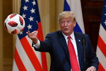 US President Donald Trump throws to his wife (unseen) a ball of the 2018 football World Cup, a gift from Russia's President Putin. Helsinki, on July 16, 2018.