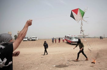Palestinian protesters flying a kite during a protest at the Gaza Strip's border with Israel.