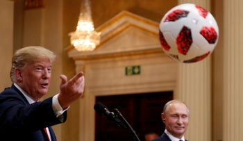 Trump throws a football to U.S. First Lady Melania during a joint news conference with Russia's President Vladimir Putin after their meeting in Helsinki, Finland, July 16, 2018