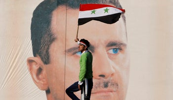 Pro-Syrian regime protester waves a Syrian flag as he stands in front of portrait of Syrian President Bashar Assad, in Damascus, Syria, December 2, 2011