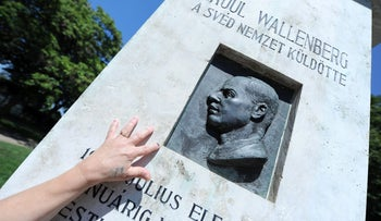 A Hungarian woman touches the memorial stone of late Swedish diplomat Raoul Wallenberg in St. Istvan park of Budapest on August 1, 2012 prior to the 100th anniversary of Wallenberg's birthday at August 4. Wallenberg, known for rescuing tens of thousands of Hungarian Jews from the holocaust, disappeared without a trace after the Soviet occupation of Budapest in 1945.