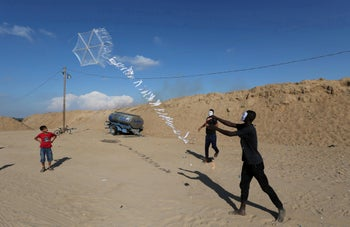 Palestinians flying a kite loaded with flammable material to be thrown at the Israeli side near the border.
