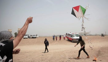Palestinians fly a kite with a burning rag dangling from its tail during a protest at the Gaza Strip's border with Israel, April 20, 2018.