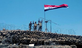 In this photo released Tuesday, July 17, 2018, by the Syrian official news agency SANA, Syrian troops flash the victory sign next to the Syrian flag in Tell al-Haara, the highest hill in the southwestern Daraa province, Syria.
