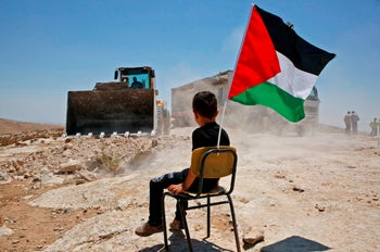 A Palestinian boy sits on a chair with a national flag as Israeli authorities demolish a school site in the the West Bank village of Yatta, south of Hebron. July 11 2018