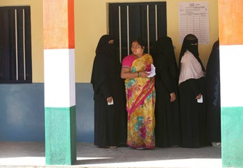 An Indian Hindu woman stands with burqa clad Muslim women as they wait outside a polling station to cast their votes in Bangalore, India. May 12, 2018