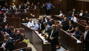 Arab lawmakers tear up copies of the nation-state law in the Knesset, July 19, 2018.