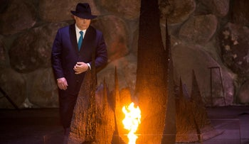 Hungarian Prime Minister Viktor Orban rekindles the eternal flame during a memorial ceremony at the Yad Vashem Holocaust Memorial in Jerusalem, July 19, 2018.