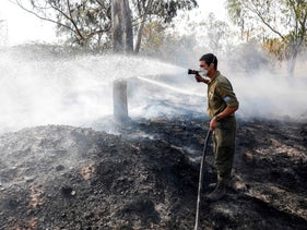 An Israeli soldier attempts to extinguish a fire in a forest field near Kibbutz of Nahal Oz, along the border with the Gaza Strip, on July 17, 2018.