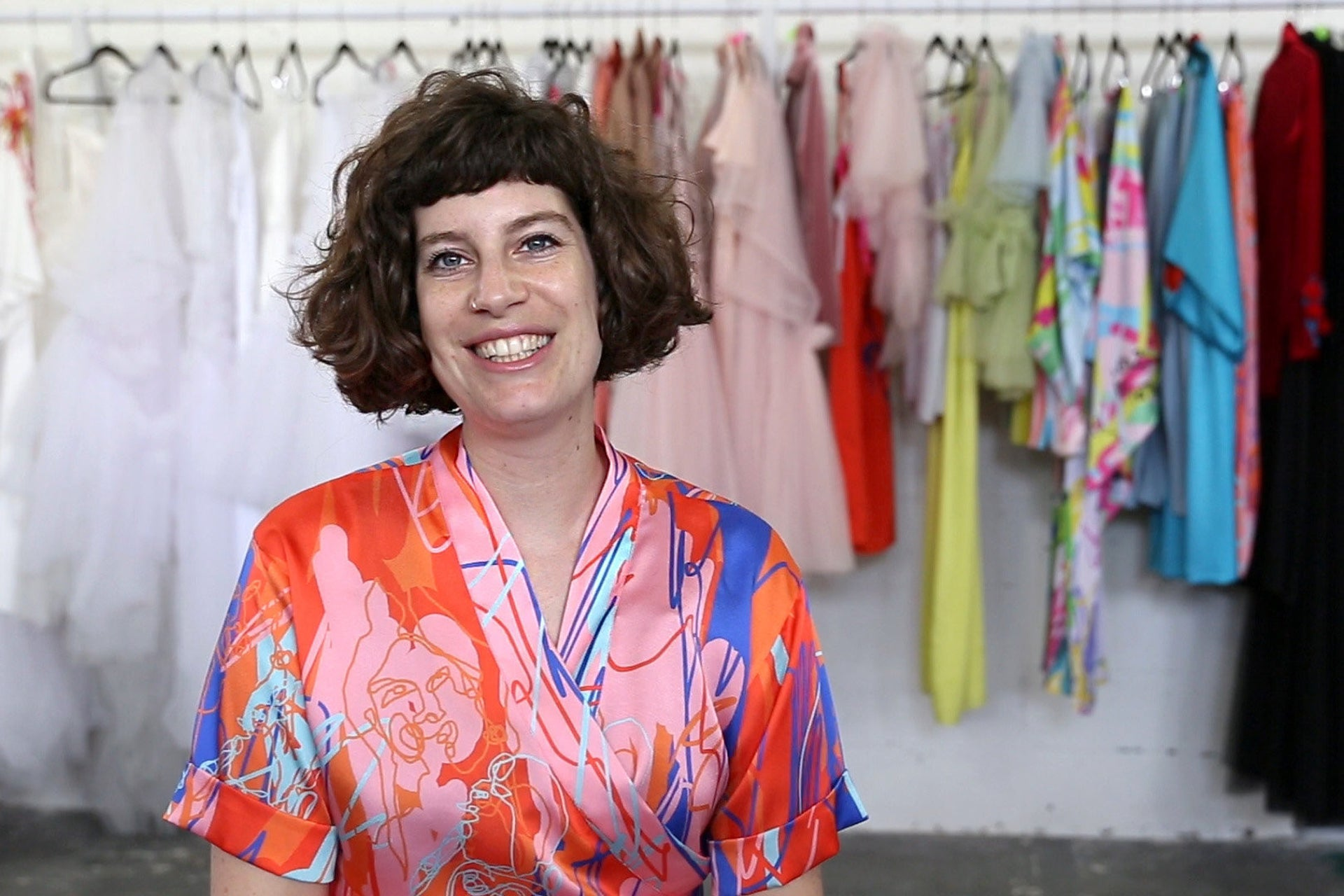 Israeli designer Shahar Avnet wearing a multicolored kimono and smiling, in her south Tel Aviv studio with a rack of her designs behind her.