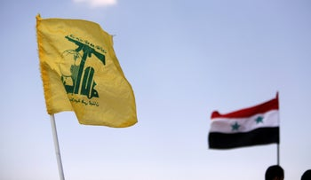 File photo: Hezbollah and Syrian flags are seen fluttering in Fleita, Syria August 2, 2017.
