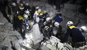 This photo provided on Jan. 7, 2018 by the Syrian Civil Defense White Helmets, which has been authenticated based on its contents and other AP reporting, shows Civil Defense workers inspecting a damaged building after a bombing that targeted the office of Ajnad al-Koukaz, a militant group consisting of foreign fighters in Idlib, Syria.