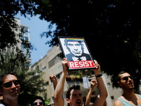 A man holding a placard with the photo of Israeli Prime Minister Benjamin Netanyahu, during a LGBT protest in Tel Aviv, July 22, 2018.