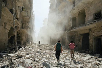Men inspect the damage after an airstrike on the rebel held al-Qaterji neighborhood of Aleppo, Syria September 25, 2016