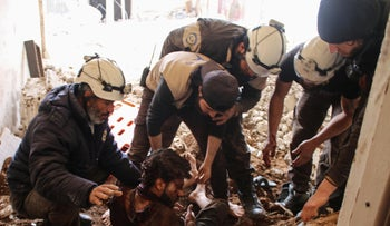 Members of the group White Helmets remove a victim from the rubble in southern Syria, April 8, 2017.