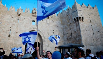 In this Sunday, May 13, 2018, file photo, Israelis wave national flags outside the Old City's Damascus Gate, in Jerusalem.