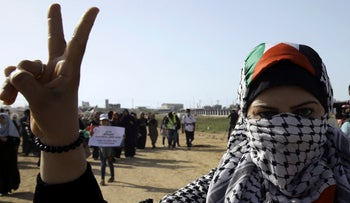 A Palestinian protester woman wearing a scarf in the colors of the national flag, gestures while marching toward the Gaza Strip's border with Israel, during a protest east of Gaza City, Tuesday, July 3, 2018.