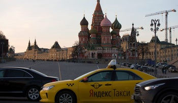A yellow Yandex NV taxi cab waits for customers beside Red Square and Saint Basil's cathedral in Moscow, Russia, on Monday, April 9, 2018.