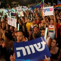 """Demonstration in Tel Aviv by members of the LGBT community, holding signs reading """"equality,"""" in protest of what is seen as discriminatory surrogacy legislation, July 22, 2018."""