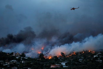 A firefighting helicopter flies over a wildfire raging in the town of Rafina, near Athens, Greece, July 23, 2018.