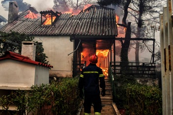 A firefighter stands in front of a burning house during a wildfire in Kineta, near Athens, on July 23, 2018.
