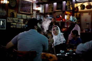 A young Syrian woman takes a selfie at the al-Nafurah Cafֳ© in the old city of Damascus, Syria, Saturday, July 14, 2018.