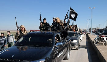 Islamic State militants pass by a convoy in Tel Abyad, Syria, on May 4, 2015