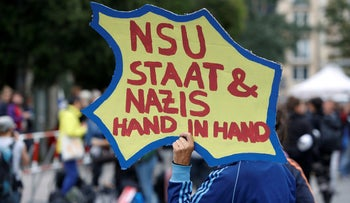 "A person holds a placard reading ""NSU state & Nazis hand in hand"" in front of a Munich court before judges give their verdict in the trial of suspected NSU neo-Nazi gang member Beate Zschaepe in Munich, Germany July 11, 2018."