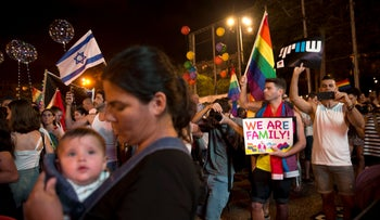 Israelis wave flags and hold signs during a rally to protest against inequality for the LGBT community in Tel Aviv, Israel, Sunday, July 22, 2018