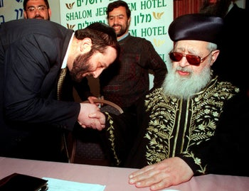 Aryeh Deri, a political kingmaker and head of the ultra-Orthodox Shas party, holds the hand of the party's spiritual leader, Rabbi Ovadia Yosef, at a women's conference in Jerusalem, March 2013