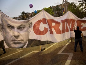 An Israeli holds a banner showing Israeli Prime Minister Benjamin Netanyahu during a rally to protest against inequality for the LGBT community in Tel Aviv, Israel. July 22, 2018