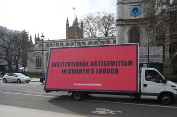 A van with a slogan aimed at Britain's Labour Party is driven around Parliament Square ahead of a debate on antisemitism in Parliament, in London, April 17, 2018