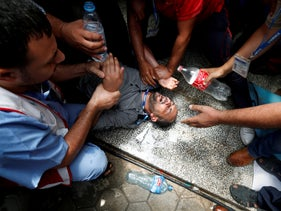 People spray water on a Palestinian UNRWA employee who tried to set himself on fire during a protest against jobs termination inside its headquarters in Gaza City. July 25, 2018
