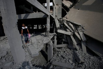 A Palestinian man looks at a building destroyed by Israeli air strikes in Gaza City. July 15, 2018