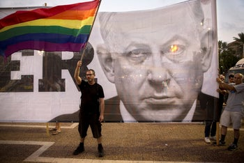 A protester waving a flag in front of a banner showing Prime Minister Benjamin Netanyahu, during a rally to protest against inequality for the LGBT community, Tel Aviv, July 22, 2018.