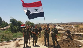 A handout picture released by the official Syrian Arab News Agency (SANA) on July 26, 2018 shows Syrian army soldiers carrying the national flag in the village of Hamidiya, Quneitra.