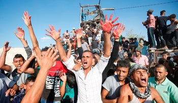 Palestinians react with bloodied hands outside a Hamas outpost that was struck by Israeli bombardment near Khan Yunis, southern Gaza Strip, July 20, 2018.