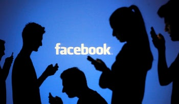 FILE PHOTO: People pose with mobile devices in front of projection of Facebook logo.