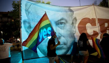 An Israeli walks with a flag in front of a banner showing Israeli Prime Minister Benjamin Netanyahu during a rally to protest against inequality for the LGBT community in Tel Aviv, Israel, Sunday, July 22, 2018.