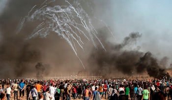 Palestinian protesters gather as tear gas canisters are launched by Israeli forces during a demonstration along the border between Israel and the Gaza strip, July 27, 2018.