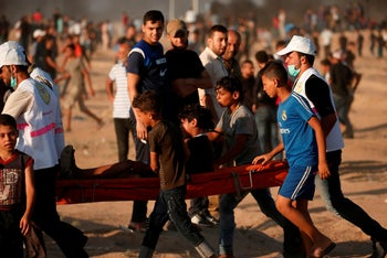 Palestinian protesters carry a youth injured during a demonstration along the border between Israel and the Gaza strip, July 27, 2018.