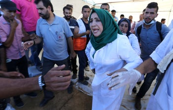 A Palestinian nurse reacts upon seeing the body of her husband who was killed by Israeli troops during a protest at the Israel-Gaza border, southern Gaza Strip, July 27, 2018.