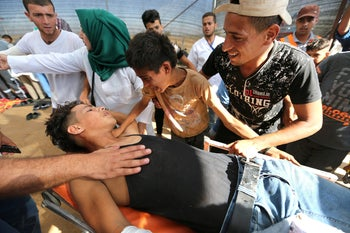 Palestinians react next to a wounded man during a protest at the Israel-Gaza border, in the southern Gaza Strip, July 27, 2018.