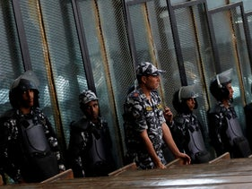 Police officers stand guard inside the court as suspects are seen behind a fence in Cairo, Egypt July 28, 2018.