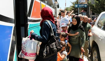 Syrian refugees walk with their belongings as they prepare to board a bus at the Masnaa crossing on the Lebanon-Syria border, July 28, 2018, returning them back to Syria.