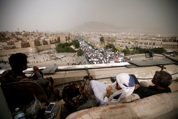 Houthi fighters watch from the roof of a building as they secure the site of a rally, Sanaa, Yemen July 13, 2018.