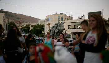 Residents get their photos taken with parrots at the Eid al-Adha carnival in a Druze village in northern Israel, September 6, 2017.